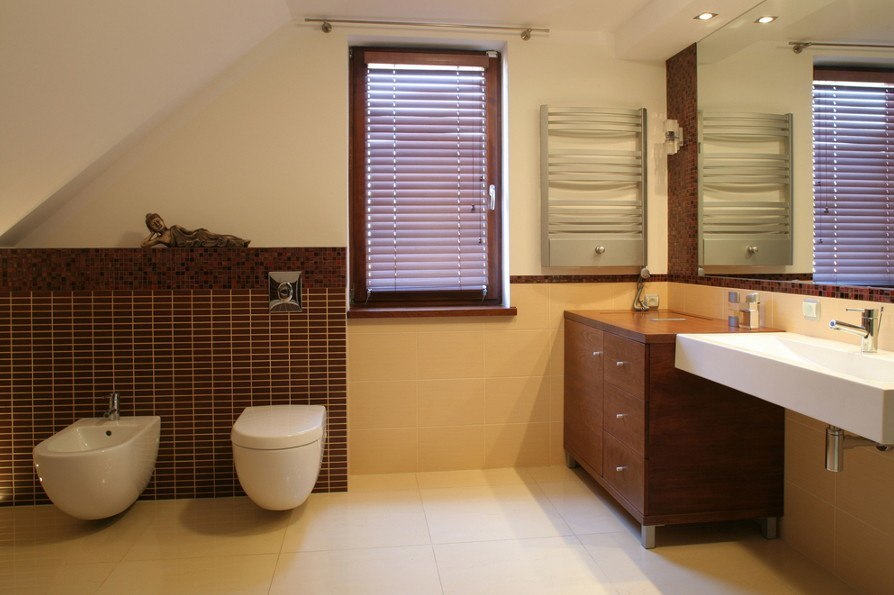 Hier ist ein Bad mit Schräge gestaltet im Fliesenmix und Designermöbeln.