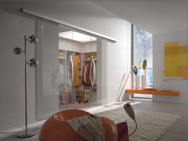 Ein begehbarer Kleiderschrank in U-Form mit weißer Oberfläche hinter Ganzglasschiebetür
