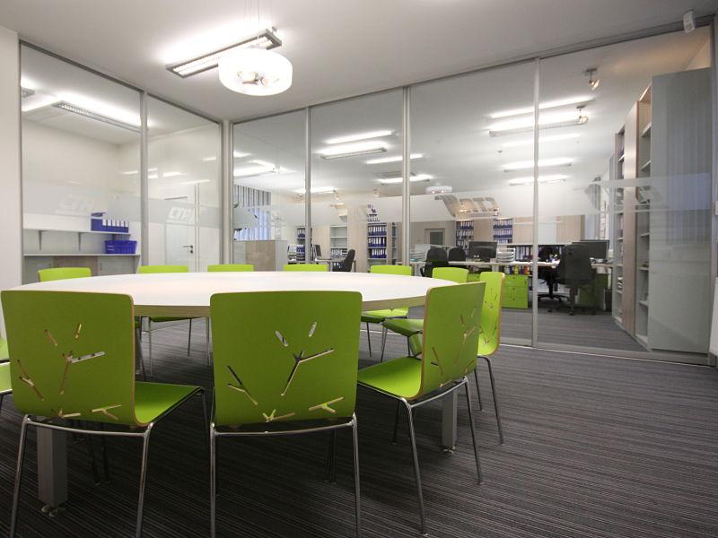 Hier begrenzen große raumhohe Glasschiebetüren einen Besprechungsraum. Die Türen sind mit dem Firmenlogo versehen.