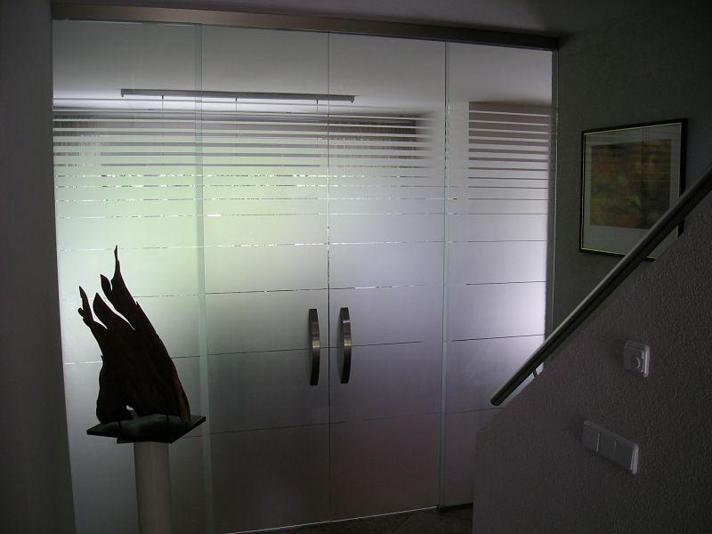 Um den Flur abzuteilen findet hier eine zweiflüglige Glasschiebetür Verwendung. Sie ist mit horizontalen Satinstreifen versehen.