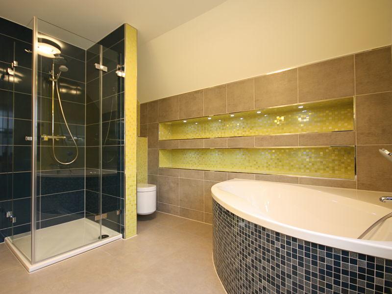Mit der Innenausbauidee, Regale in die Wand einzubauen, ergibt sich viel praktische Ablagefläche im Bad