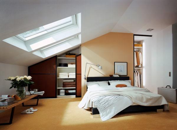 Ein Schlafzimmer mit begehbarem Kleiderschrank unter der Dachschräge eingerichtet