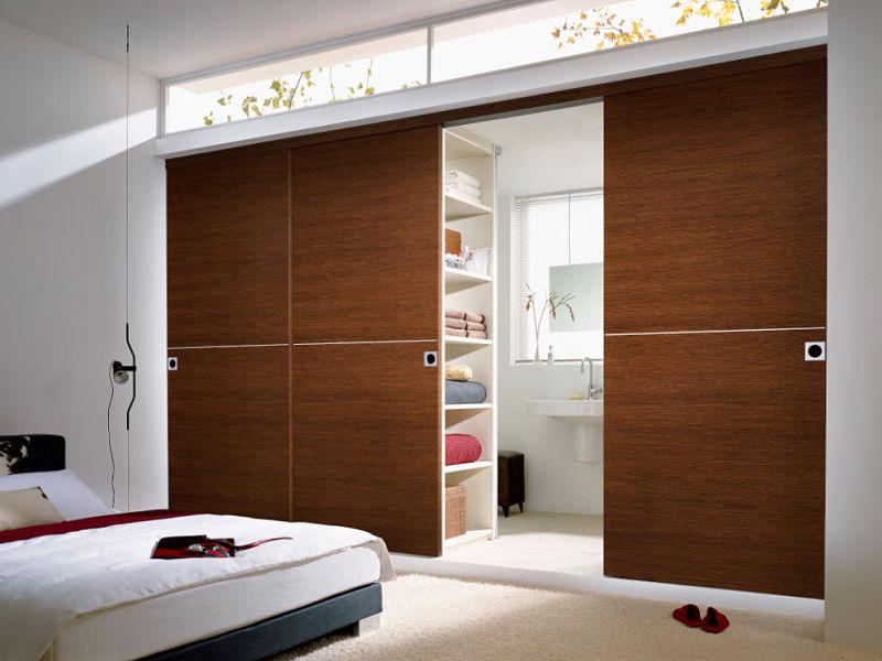 Eleganter Raumteiler aus Holz zwischen Bad und Schlafzimmer