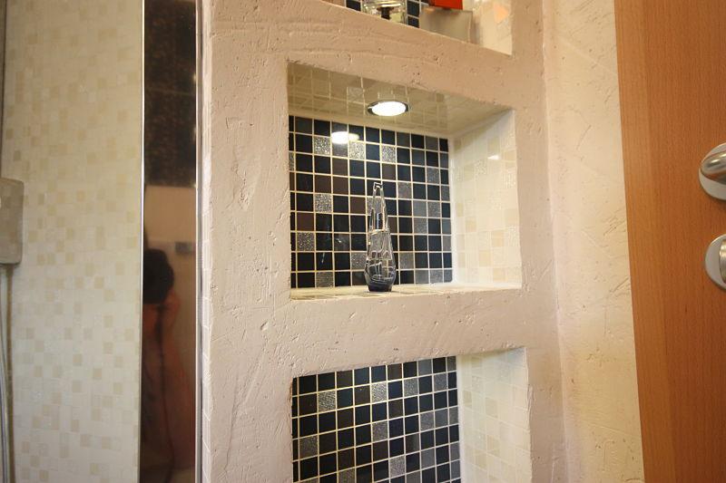 Ein individuelles Regal im Bad bauten wir mithilfe einer Trockenbaukonstruktion. Diese haben wir mit einer mediterranen Spachteltechnik beschichtet und mit kleinen Spots versehen.
