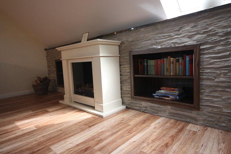 Mit einer Wandverkleidung in Steinoptik haben wir den Drempel genutzt. Eingearbeitete Bücherregale bilden einen schönen Blickfang.