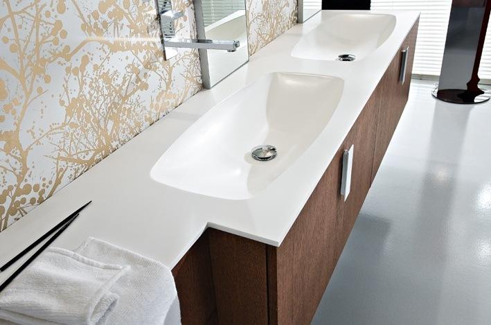Ein großer einheitlicher Waschtisch in Weiß und ein Unterschrank aus edlem Holz charakterisieren diese Designerbadmöbel-Komposition.
