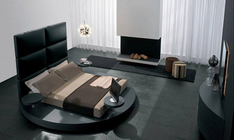 Moderne Schlafzimmer – Ein Schlafzimmer mit exklusivem runden Bett und einem modernen Kamin