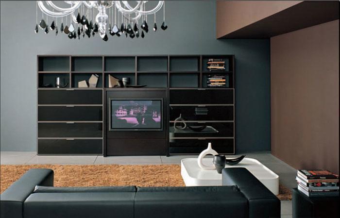 Eine dezent schlichte Wohnwand mit dunkler Wandfarbe zeichnet dieses moderne Wohnzimmer aus