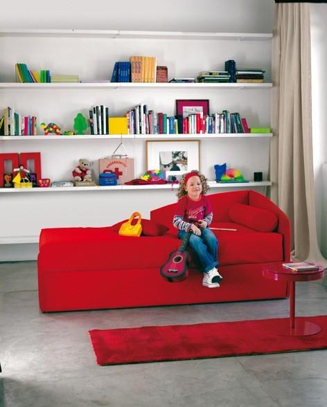 Kinderzimmergestaltung - Ein Kuschelteppich und ein rotes Sofa, da freuen sich junge Damen. Da macht das Aufräumen sicher gleich viel mehr Spaß.