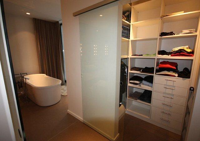 Hinter Glasschiebetüren befindet sich ein weiteres kleines Ankleidezimmer.