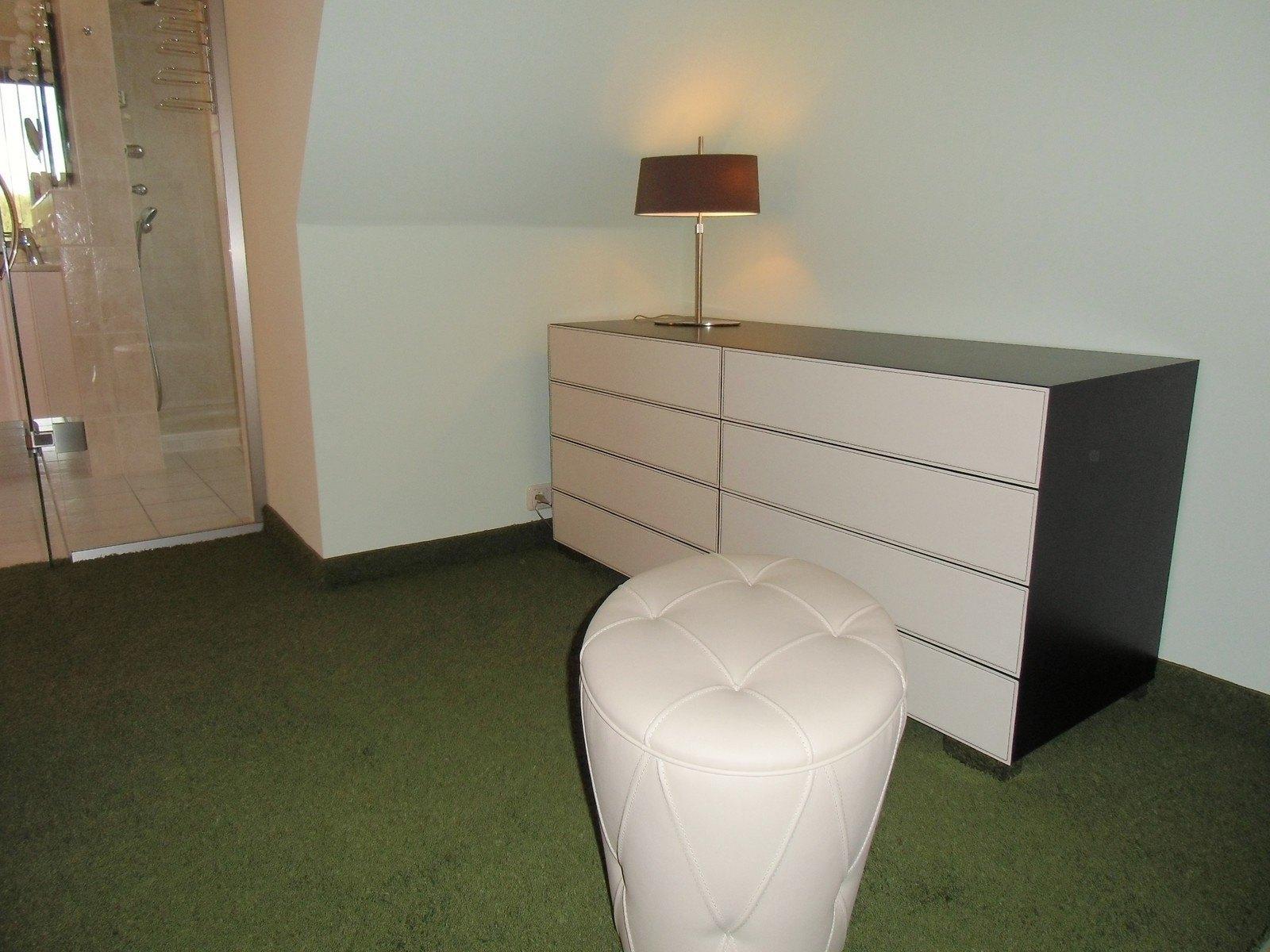 Die Kommode im Ankleidezimmer ist ein edles Modell. Die Fronten der Schubkästen sind aus Kernleder.