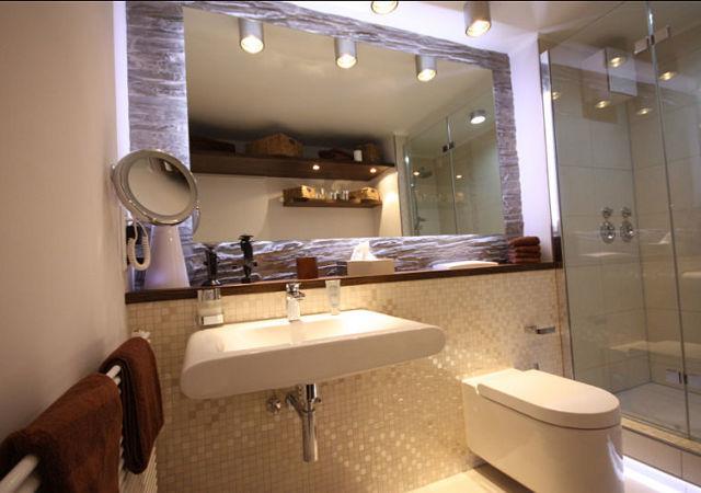 Badezimmer mit einer Wandgestaltung in Steinoptik und einem Spiegel inklusive Beleuchtung