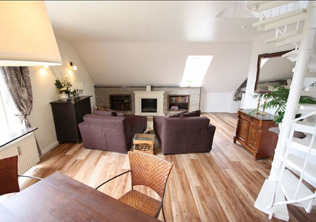 Das Ergebnis des Dachgeschoss-Umbaus ist ein gemütliches Wohnzimmer mit Kamin