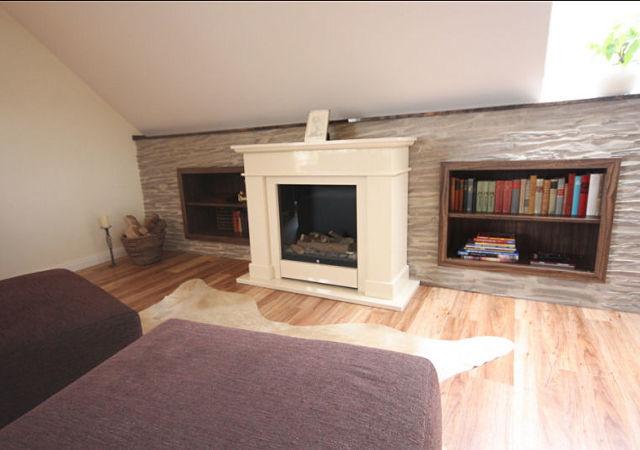 Dachgeschossausbau mit Wandpaneelen in Steinoptik und mit zusätzlich eingebautem Regal