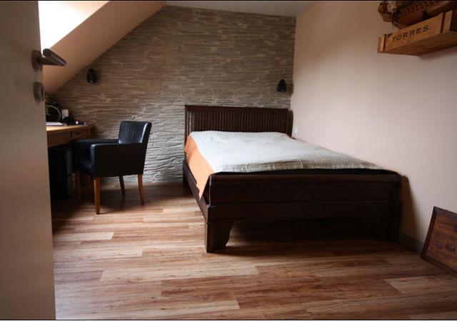 Die Schlafzimmereinrichtung ist nach dem Dachausbau viel gemütlicher. Eine Wandverkleidung in Steinoptik gibt dem Raum ein rustikales Flair
