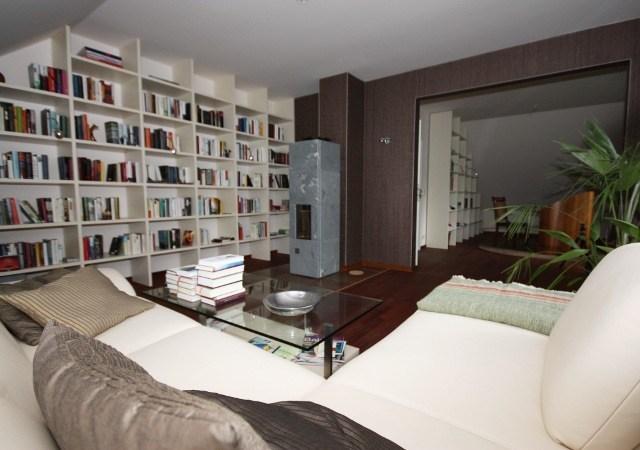Nach dem Dachgeschossausbau wurde aus dem Abstellraum ein geschmackvolles Lesezimmer mit Parkettfußboden, modernem Kamin und maßgefertigten Einbaumöbeln.