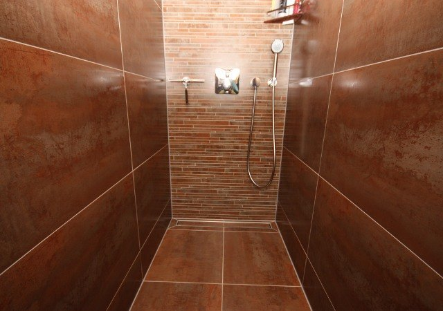 Aus dem alten Bad im Dachgeschoss wurde ein ganz Modernes, mit begehbarer, großzügiger Dusche. Mediterrane Farbverläufe wirken sehr wohnlich.