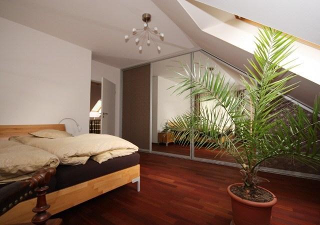 Hier wird das Schlafzimmer mit Schräge praktisch genutzt. Hervorragend geeignet ist der moderne Einbauschrank mit Schiebetüren.