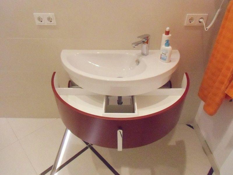 Ein halbrundes Waschbecken mit praktischem Unterschrank für die Aufbewahrung von Kosmetikartikeln