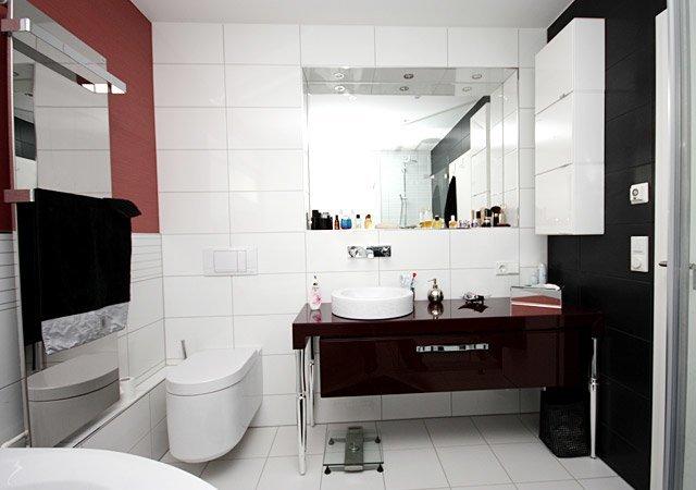 Das Designerbad wirkt modern und aufgeräumt. Der Waschtisch ist aus bordeauxrotem Hochglanzlack