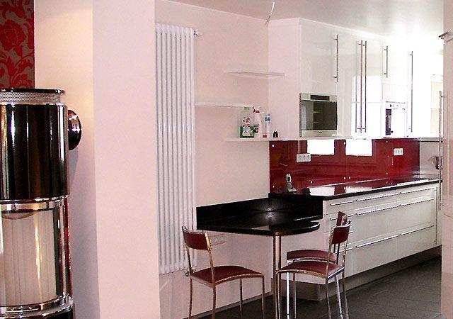 Haus einrichten - Die moderne Küche mit rotem Farbtupfer und hochglanzlackierten Fronten passt perfekt zum Wohnzimmer