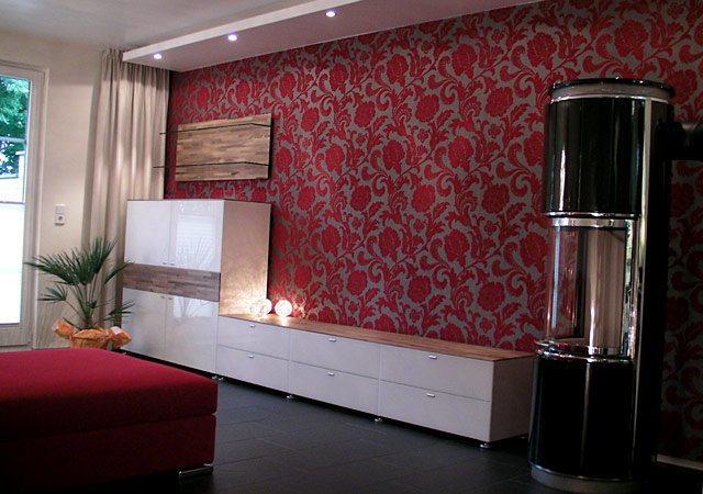 Haus einrichten - Eine hochwertige Tapete mit roten florem Muster gibt eine perfekten Kontrast zur weißen Wohnwand und dem modernen Kamin.