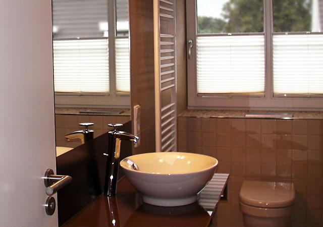 Haus einrichten - Das neue Bad mit Blick zum Fenster. Moderne Armaturen, viele Glas und schicke Fliesen machen die Verwandlung perfekt.