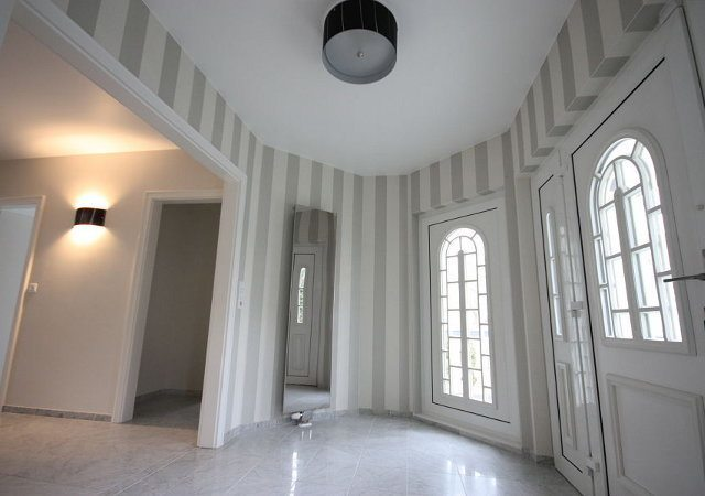 Haus renovieren - Den Eingangsbereich gestalteten wir mit Tapete im Streifendesign und einem Designheizkörper als Spiegel sehr viel moderner.