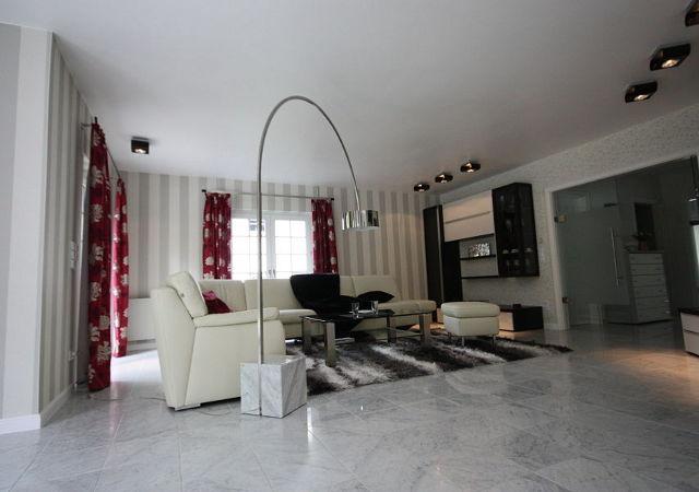 Haus renovieren - Blick zur gemütlichen Sitzecke mit Ledermöbeln, einem kuschligen Teppich und einer modernen Wohnwand