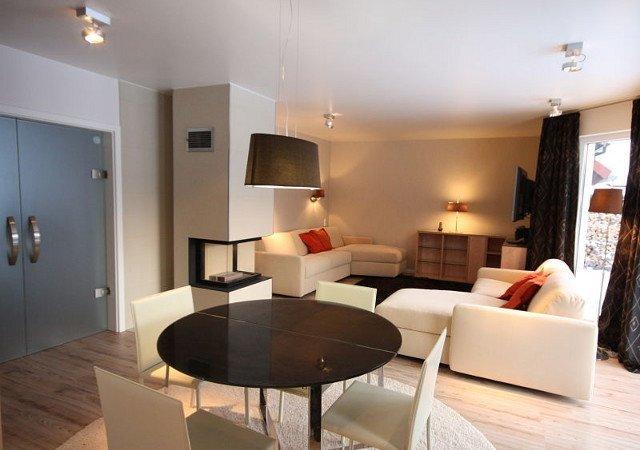 Wohnzimmereinrichtung - Ein Blick vom runden Esstisch zum Kamin und zur Sitzecke. Links im Bild die moderne Glastür und ein durchgängig schicker Bodenbelag - ohne Stufen!