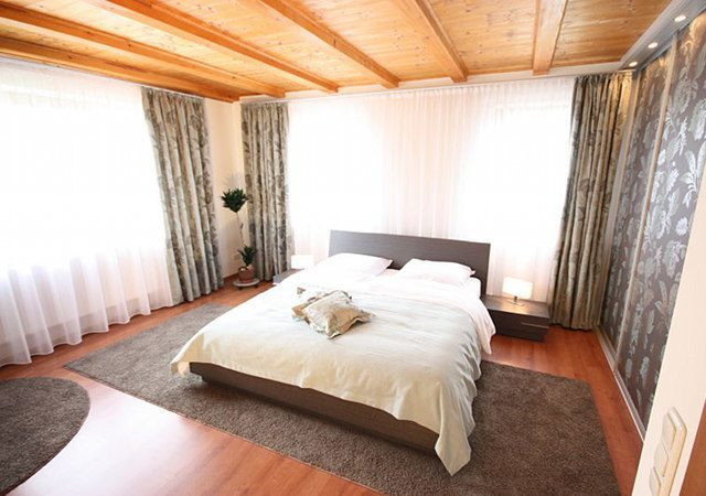 Passende Gardinen, Übergardinen, ein Bettschal, Kissen und die Schiebetüren machen aus dem Schlafzimmer einen individuell gestalteten Raum.