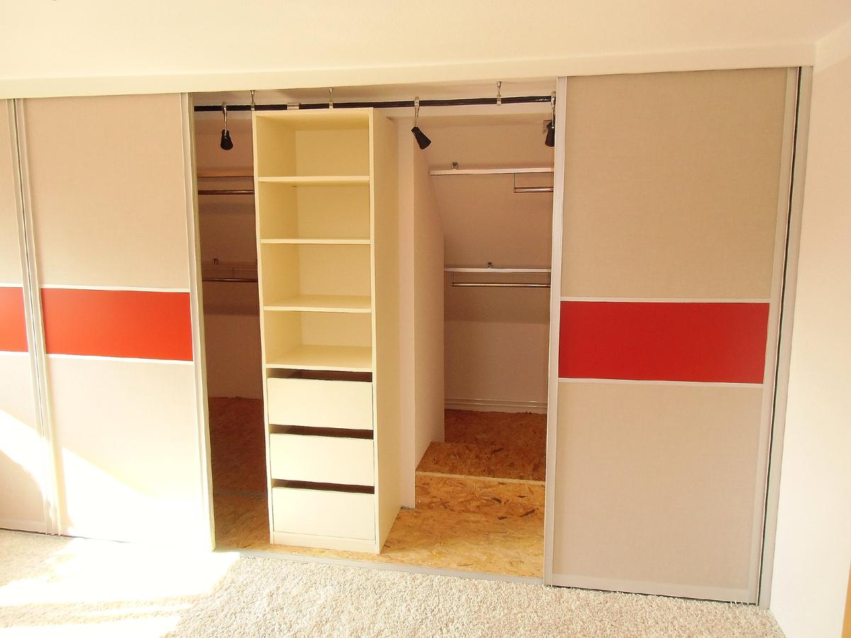 Schlafzimmergestaltung - Hinter der Schiebetüranlage befinden sich praktische verschiebbare Kleiderstangen und die Beleuchtung.
