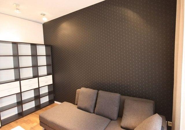 Wohnung einrichten -Mit einer dunkelgrauen Designtapete mit zartem grafischen Muster in Silber, entstand eine eindrucksvolle Wand.