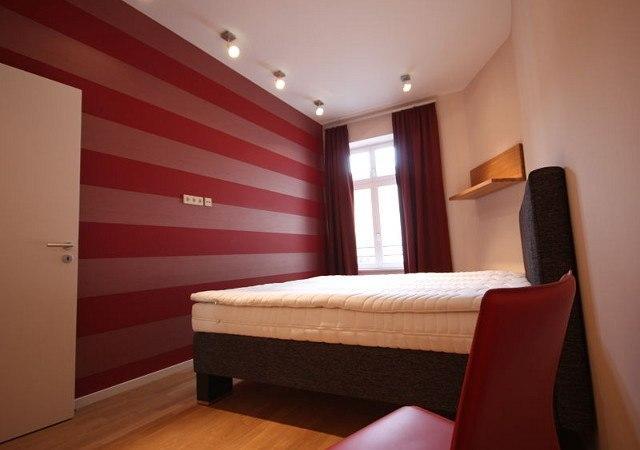 Wohnung einrichten .Das Gästezimmer besticht durch die Tapete, die wir in diesem Fall quer verklebten. Ein großes gemütliches Bett darf natürlich nicht fehlen.