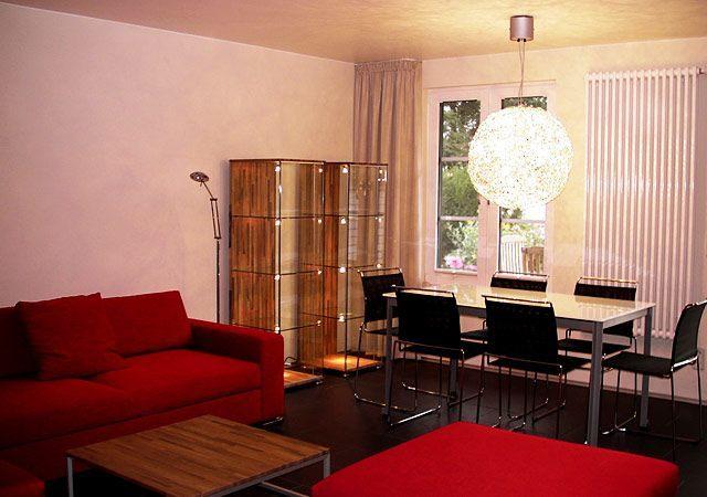 Haus einrichten - in rotes Sofa als Farbtupfer kombiniert mit Holz, Glas und verchromten Details ergeben ein harmonischen Gesamteindruck