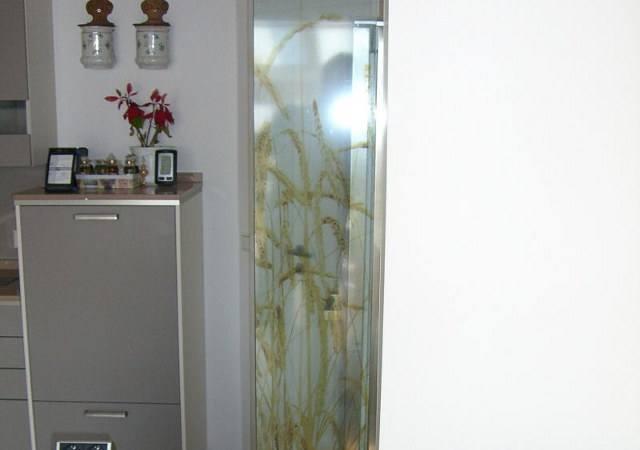 Lackierte Glaselemente dienen als schmaler Raumteiler zwischen Küche und Wohnzimmer