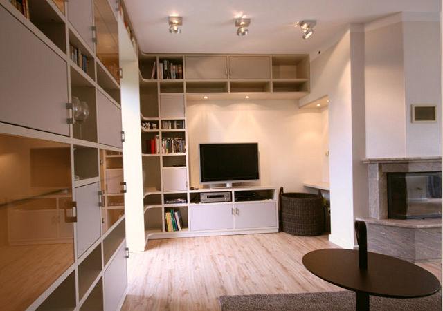 Wohnzimmereinrichtung - Ein Blick in die Kaminecke zeigt unsere maßgefertigte Wohnwand. Millimetergenau passt sie sich der Raumkontur perfekt an.