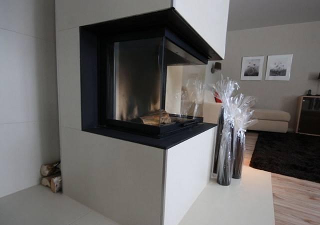 Wohnzimmereinrichtung - Eine Kaminverkleidung mit großformatigen Fliesen sieht in diesem Fall edel aus. Hinter dem Kamin gibt es Platz für Holz.