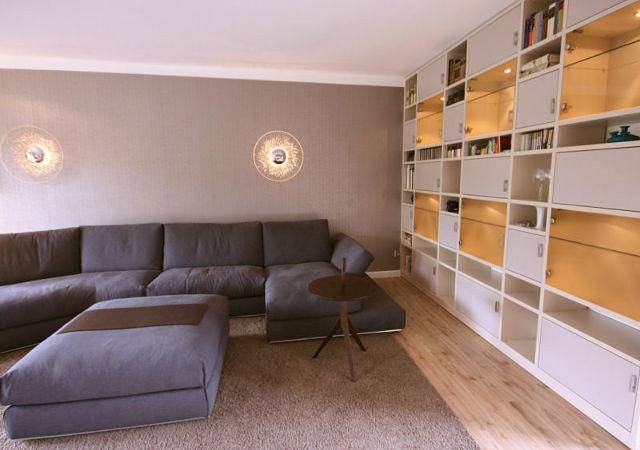 Wohnzimmereinrichtung - Die maßgefertigte Wohnwand mit indirekter Beleuchtung kombiniert mit dem blauen Sofa und einer interessanten Strukturtapete im Hintergrund verleiht dem Wohnzimmer Gemütlichkeit.