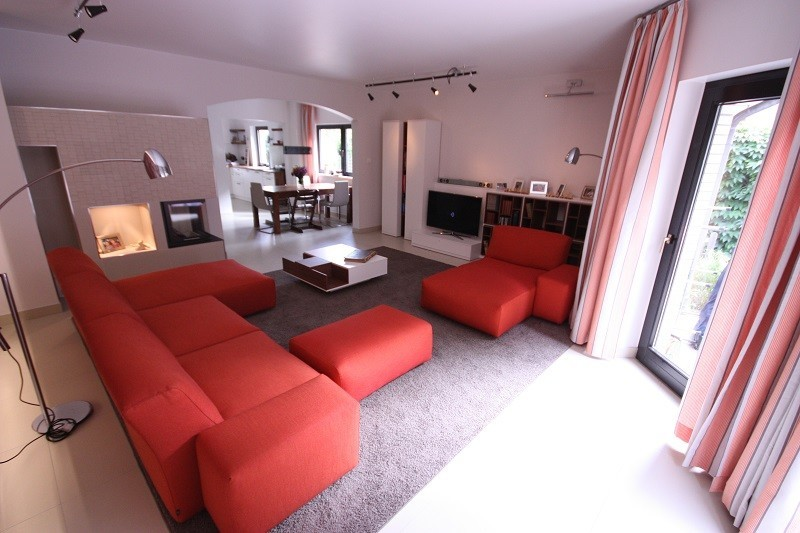 Großzügig wirkendes Wohnzimmer mit viel Licht. Ein individuell zugeschnittener Teppich und die Gardinen sorgen für Kuschelatmosphäre.