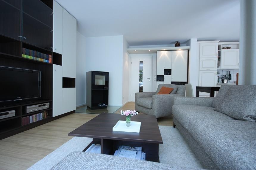 Wohnzimmergestaltung-Das neue Wohnzimmer ist mit einem getuftetem Teppich dekoriert und mit einem Designersofa eingerichtet.