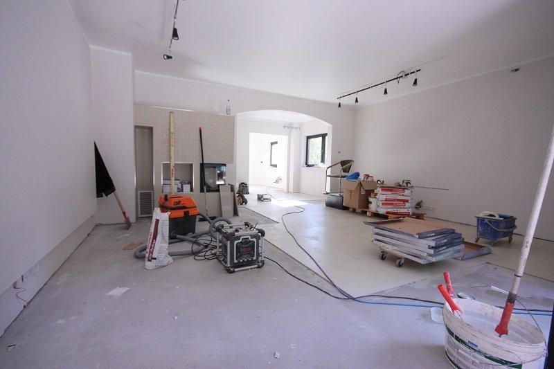 Wir sind dabei, die großformatigen Fliesen zu verlegen - nicht nur im Wohnzimmer, sondern im gesamten Erdgeschoss.