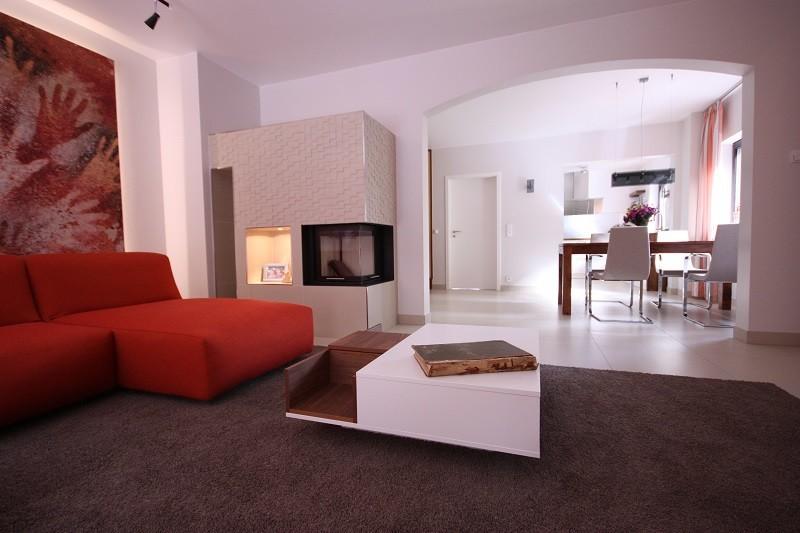 Wohnzimmergestaltung - Der extravagante Kaminofen fügt sich mit der gewählten Größe perfekt in die Raumgeometrie ein.