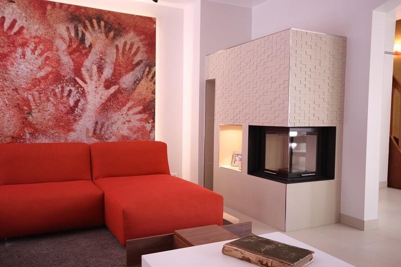 Wohnzimmergestaltung -Der extravagante Kaminofen fügt sich mit der gewählten Größe perfekt in die Raumgeometrie ein.