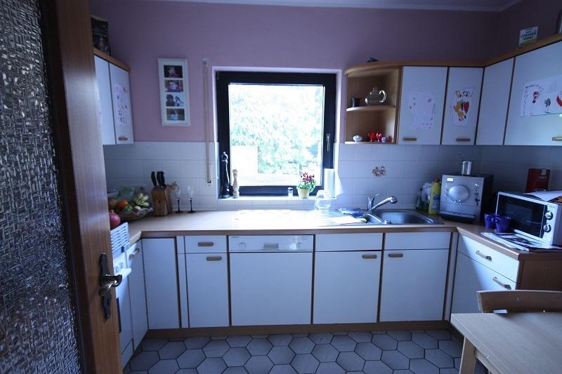 Unmoderne Küchenmöbel, alte Holzgriffe und ein brauner Fliesenfußboden brauchen eine Verjüngungskur.