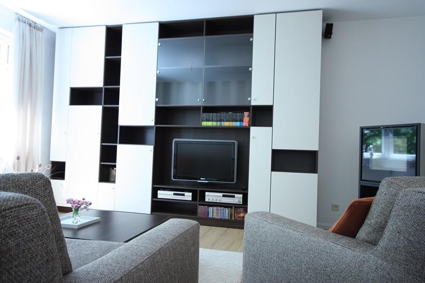 Wohnzimmergestaltung-Hier sehen Sie die von unseren Innenarchitekten entworfene Wohnwand, die sich der Raumgeometrie perfekt anpasst.
