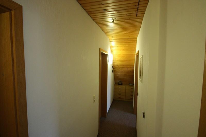 Vorher - So sah der dunkle lange Flur vorher aus. Die Decke war mit Holz vertäfelt.