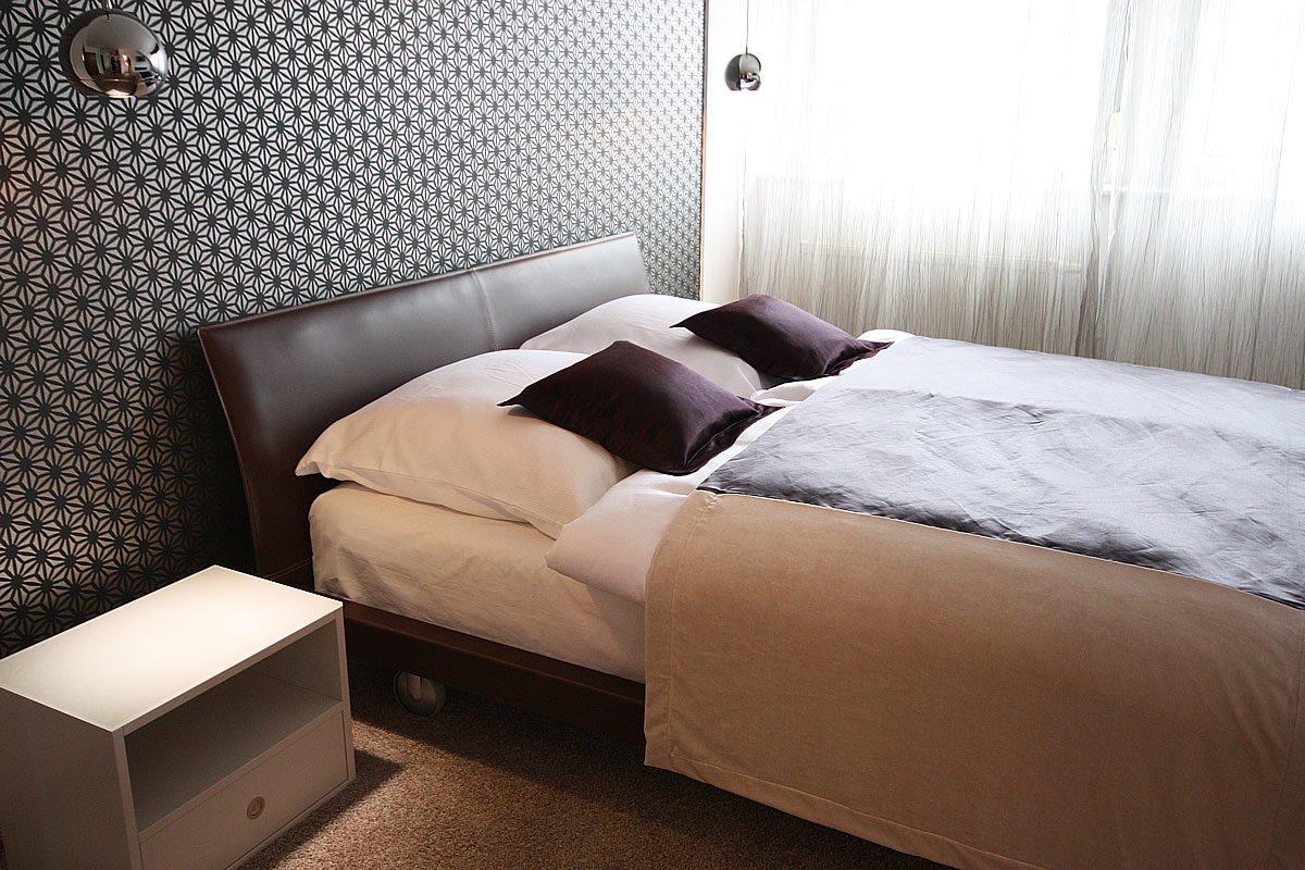 Schlafzimmereinrichtung - Die grafische Designtapete vermittelt einen interessanten Kontrast zum zarten Gardinenstoff.