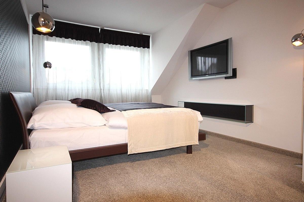 Schlafzimmereinrichtung - Eine ansprechende Farbgestaltung erzeugen eine wirklich gemütliche Atmosphäre. Gardinen, Kissen und Tagesdecke runden das Bild ab.