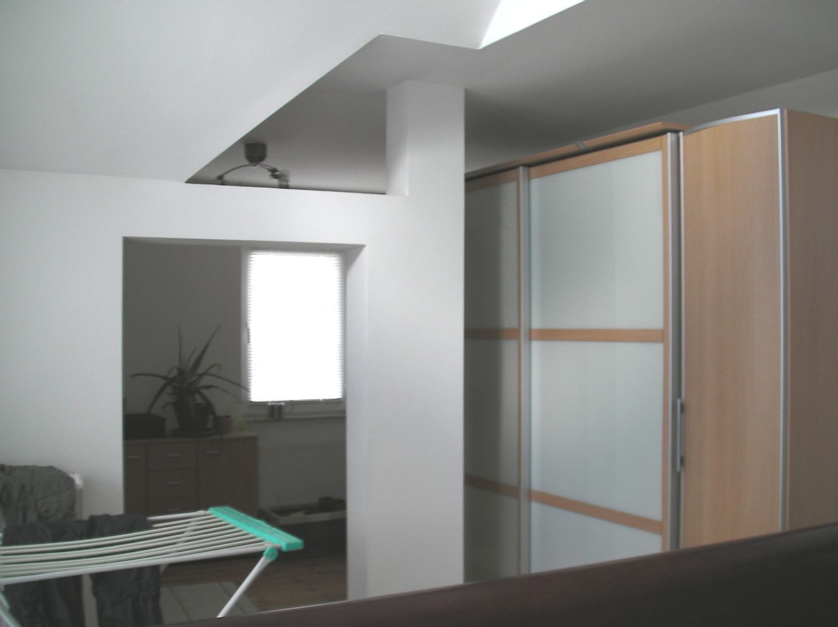 Der Schrank steht hinter einem störenden Pfeiler und die Zimmerdecke hat viele Ecken und Kanten.
